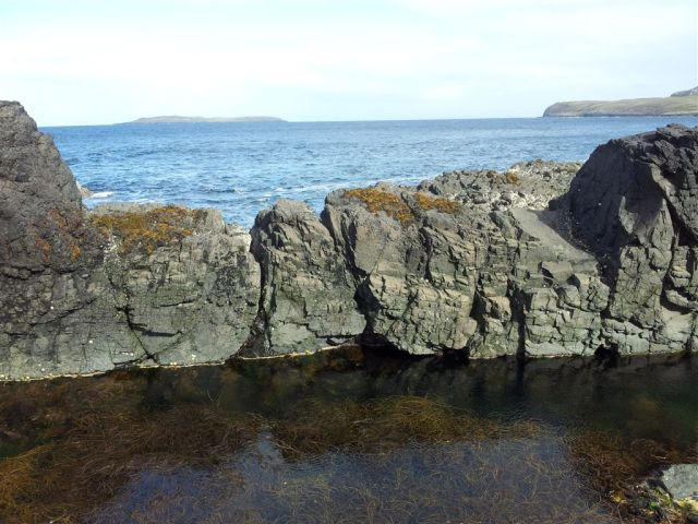 Crystal clear sea pools, the isle of Eilean Trodday over the sea