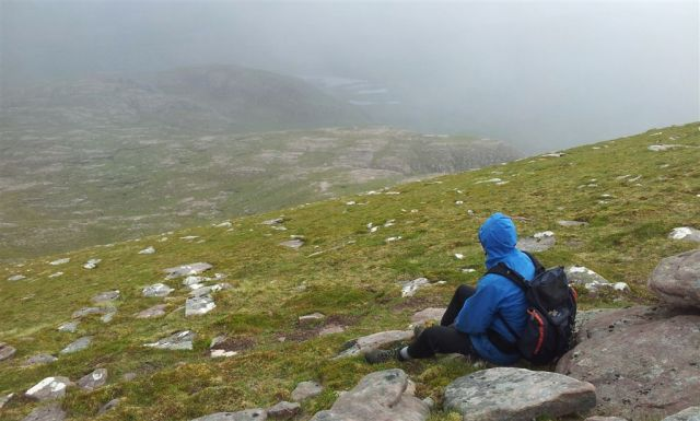 Sheltering at the not so sheltered spot near the summit looking east over descent Plan A